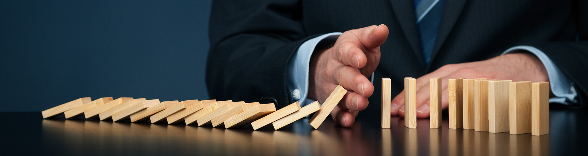 dominoes falling over to suggest risk