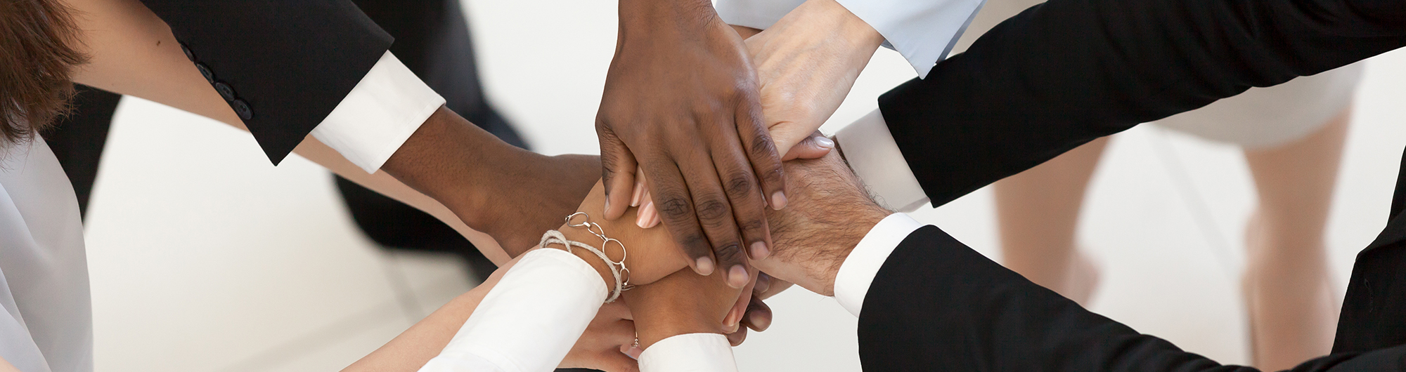people of various races clasping hands to show diversity